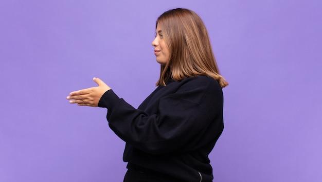 Młoda blond kobieta uśmiecha się, wita cię i oferuje uścisk dłoni, aby zamknąć udaną transakcję, koncepcja współpracy