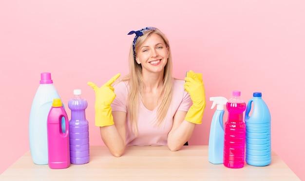 Młoda blond kobieta uśmiechając się pewnie wskazując na swój szeroki uśmiech. koncepcja gospodyni