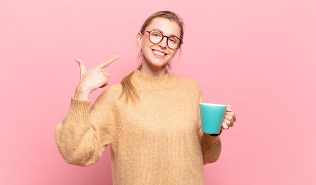 Młoda blond kobieta uśmiechając się pewnie wskazując na własny szeroki uśmiech, pozytywne, zrelaksowane, zadowolone nastawienie. koncepcja kawy