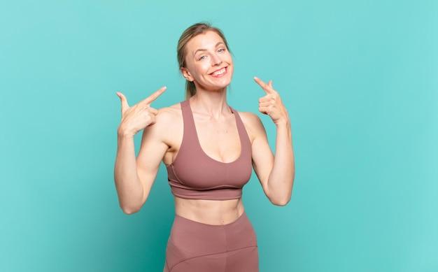 Młoda blond kobieta uśmiechając się pewnie wskazując na własny szeroki uśmiech, pozytywne, zrelaksowane, zadowolone nastawienie. koncepcja sportu