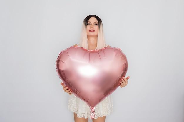 Młoda blond kobieta w białej koronkowej sukience trzymając duży różowy balon serce w dłoniach na białym tle