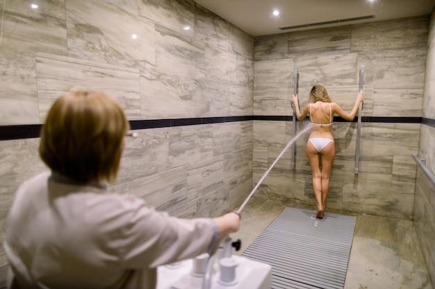 Młoda blond kobieta w białym kostiumie kąpielowym o masażu wysokociśnieniowym z prysznicem charcot do zabiegów antycellulitowych w salonie spa