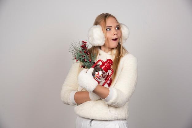 Młoda blond kobieta w białym stroju z prezentami patrząc gdzieś.
