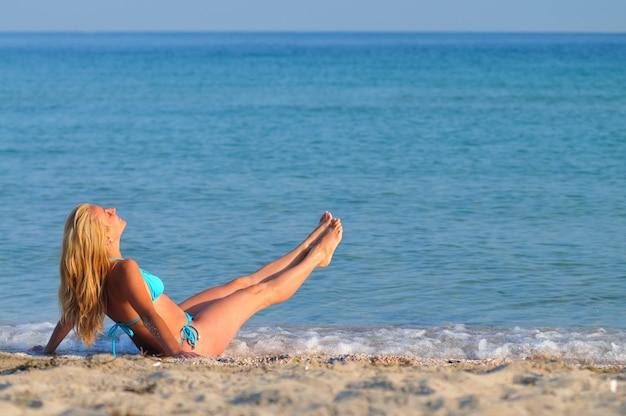 Młoda blond kobieta w bikini, siedząc nad brzegiem morza