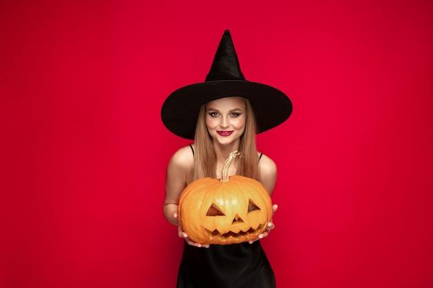 Młoda blond kobieta w czarnym kapeluszu i kostiumu na czerwonym tle. atrakcyjna kaukaska modelka. halloween, czarny piątek, cyber poniedziałek, sprzedaż, koncepcja jesień. miejsce. posiada dynię.