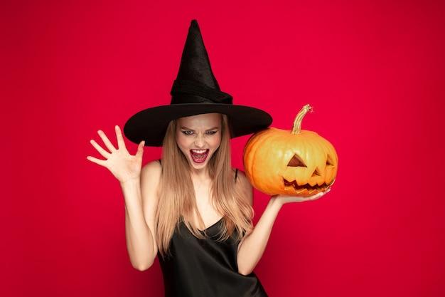 Młoda blond kobieta w czarnym kapeluszu i kostiumu na czerwonym tle. atrakcyjna kaukaska modelka. halloween, czarny piątek, cyber poniedziałek, sprzedaż, koncepcja jesień. miejsce. trzyma dynię, krzyczy.