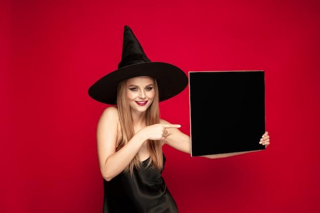 Młoda blond kobieta w czarnym kapeluszu i kostiumu na czerwonym tle. atrakcyjne kaukaski modelki pozowanie. halloween, czarny piątek, cyber poniedziałek, sprzedaż, koncepcja jesień. miejsce. mieści czarny talerz.