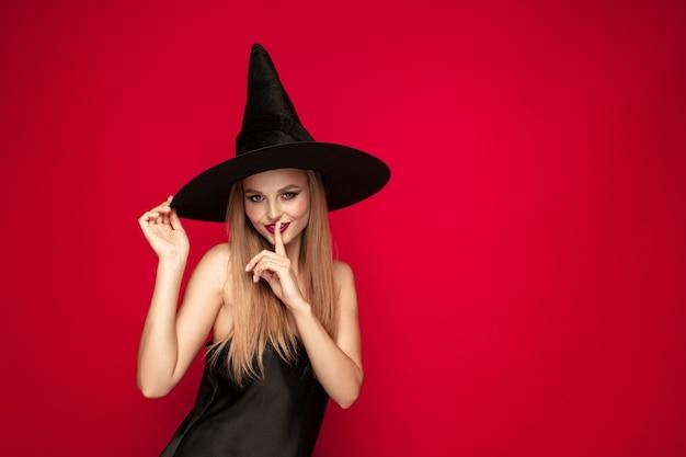 Młoda blond kobieta w czarnym kapeluszu i kostiumu na czerwonym tle. atrakcyjne kaukaski modelki pozowanie. halloween, czarny piątek, cyber poniedziałek, sprzedaż, koncepcja jesień. miejsce. szepcząc sekret.