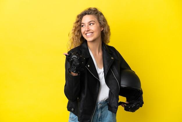 Młoda blond kobieta w kasku motocyklowym na żółtym tle, wskazując na bok, aby zaprezentować produkt