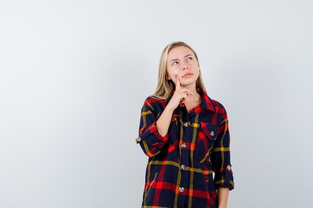 Młoda blond kobieta w kraciastej koszuli myśli