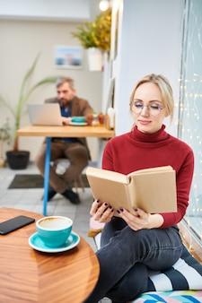 Młoda blond kobieta w okularach i casualwear czytanie książki podczas relaksu i kawy w kawiarni