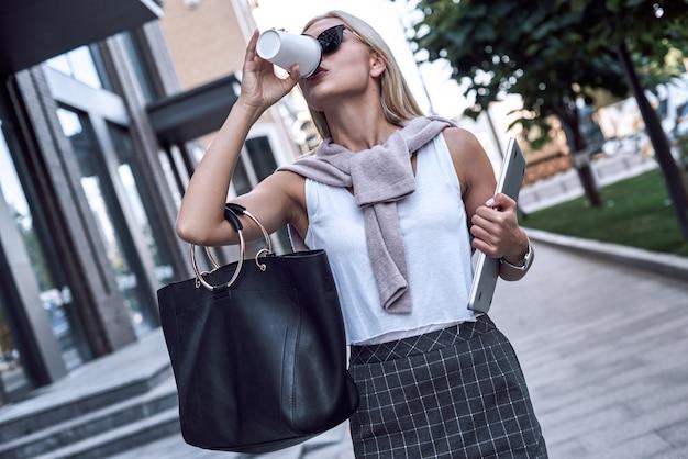 Młoda blond kobieta w okularach przeciwsłonecznych pije kawę i trzyma laptopa