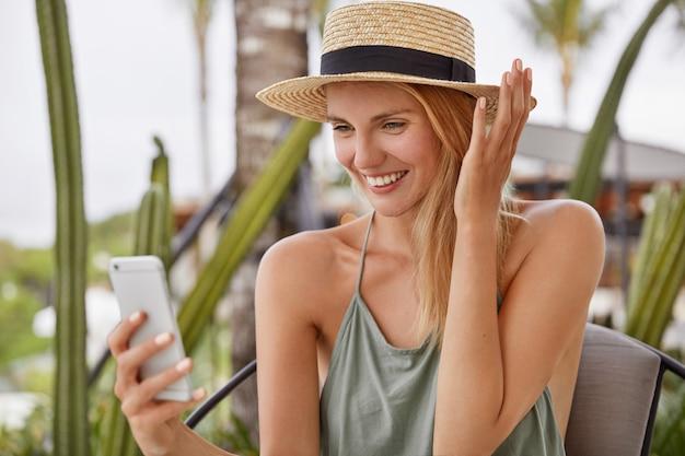 Młoda blond kobieta w słomkowym kapeluszu siedzi w kawiarni