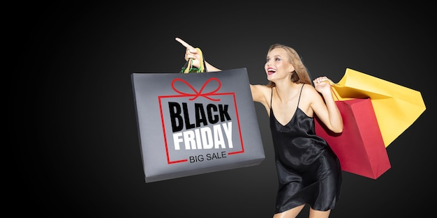 Młoda blond kobieta w sukni zakupy na czarnym tle. atrakcyjna kaukaska modelka. finanse, czarny piątek, cyber poniedziałek, sprzedaż, koncepcja jesień. miejsce. uśmiechnięty, krzyczący szczęśliwy.