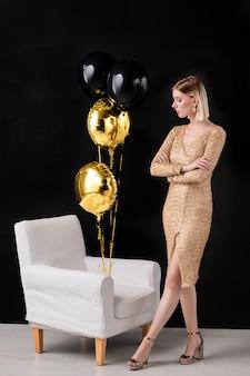 Młoda blond kobieta w złotej sukni koloru i butach na wysokim obcasie patrząc na kilka balonów przywiązanych do fotela z białej skóry