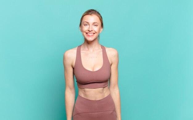 Młoda blond kobieta wygląda na szczęśliwą i głupkowatą z szerokim, zabawnym, szalonym uśmiechem i szeroko otwartymi oczami. koncepcja sportu