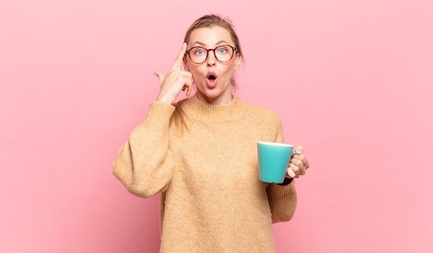 Młoda blond kobieta wygląda na zaskoczoną, z otwartymi ustami, zszokowaną, realizując nową myśl, pomysł lub koncepcję. koncepcja kawy