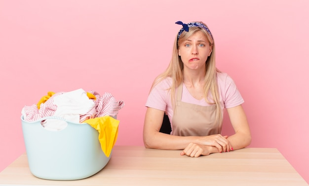 Młoda blond kobieta wygląda na zdziwioną i zdezorientowaną. koncepcja prania ubrań