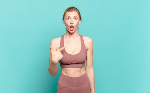 Młoda blond kobieta wygląda na zszokowaną i zaskoczoną z szeroko otwartymi ustami, wskazując na siebie. koncepcja sportu