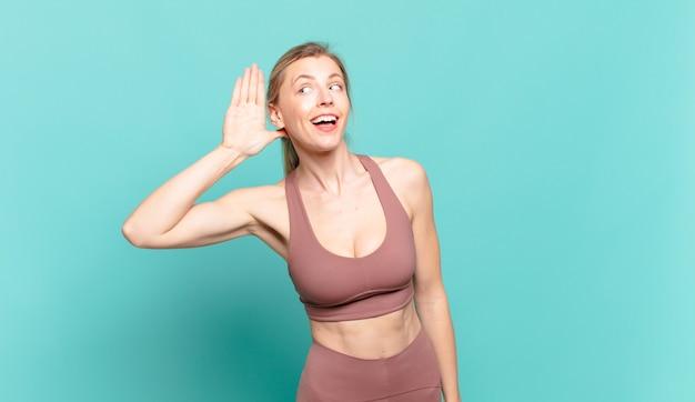 Młoda blond kobieta wygląda poważnie i ciekawie, słucha, próbuje podsłuchać tajną rozmowę lub plotki, podsłuchuje. koncepcja sportu