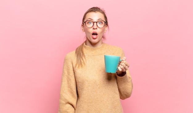 """Młoda blond kobieta wyglądająca na bardzo zszokowaną lub zaskoczoną, patrząca z otwartymi ustami i mówiąca """"wow"""". koncepcja kawy"""
