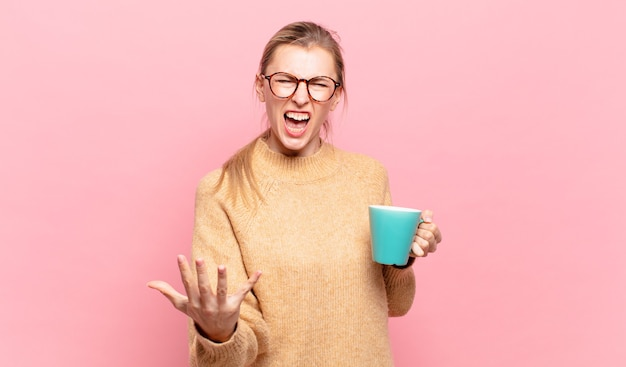 Młoda blond kobieta wyglądająca na złą, zirytowaną i sfrustrowaną, krzycząc wtf lub co jest z tobą nie tak. koncepcja kawy