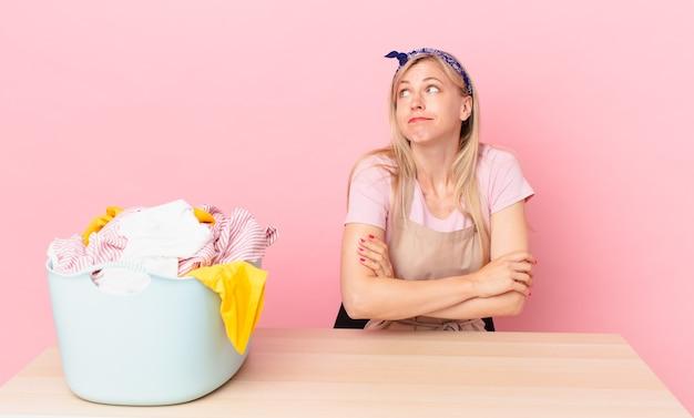 Młoda blond kobieta wzrusza ramionami, czuje się zdezorientowana i niepewna. koncepcja prania ubrań