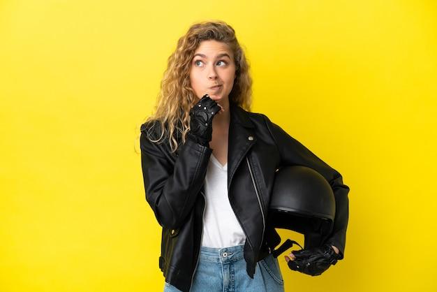 Młoda blond kobieta z kaskiem motocyklowym na białym tle na żółtym tle, mająca wątpliwości i myśląca