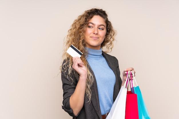 Młoda blond kobieta z kręconymi włosami na białym tle na beżowy trzymając torby na zakupy i kartę kredytową