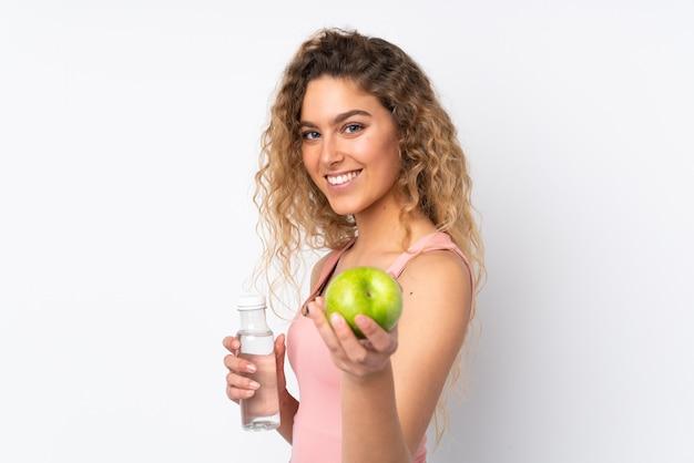 Młoda blond kobieta z kręconymi włosami na białym tle na białej ścianie z jabłkiem i butelką wody