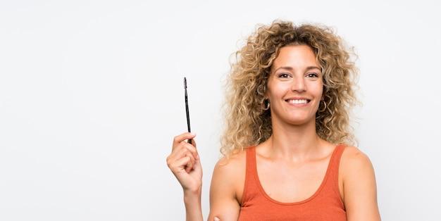 Młoda blond kobieta z kręconymi włosami stosowania tuszu do rzęs z pośpiechu kosmetycznych