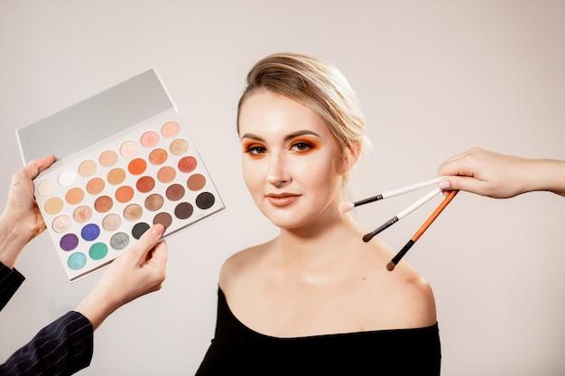 Młoda blond kobieta z pomarańczowo-brązowym jasnym makijażem. ręce trzyma różne pędzle do makijażu i paletę cieni