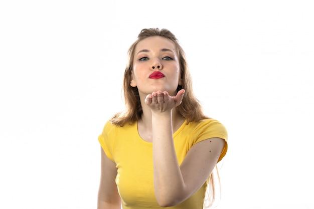 Młoda blond kobieta z żółtym t-shirt dmuchanie pocałunek