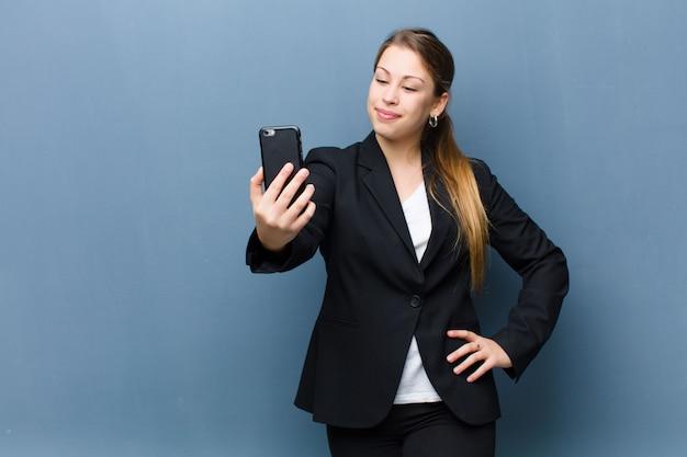 Młoda blond kobieta za pomocą smartfona na ścianie grunge