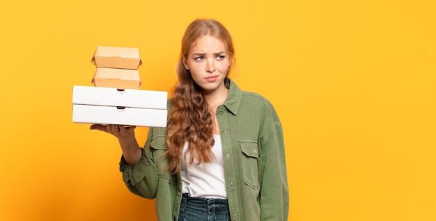 Młoda blond kobieta zabierając fast food
