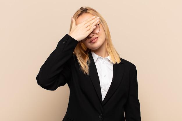 Młoda blond kobieta zakrywająca oczy jedną ręką czując się przestraszona lub niespokojna