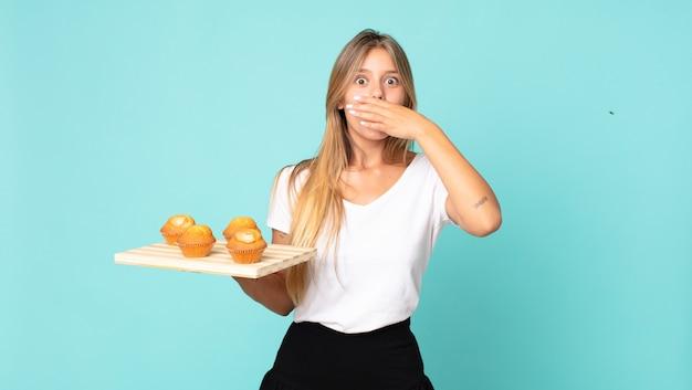 Młoda blond kobieta zakrywająca usta rękami zszokowaną i trzymającą troy babeczki