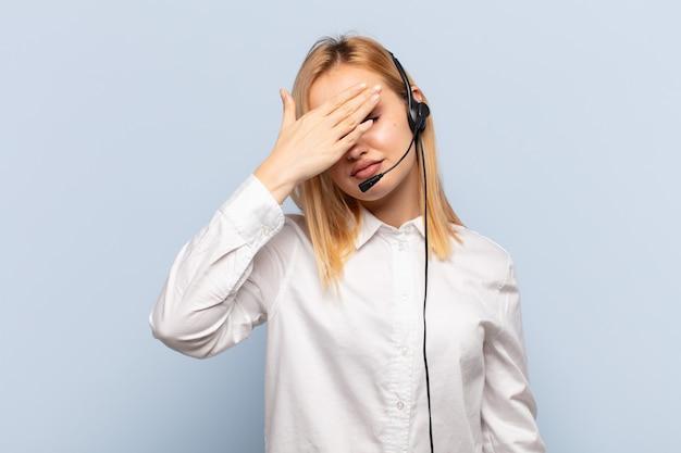 Młoda blond kobieta zasłaniająca oczy jedną ręką czując się przestraszona lub niespokojna, zastanawia się lub ślepo czeka na niespodziankę