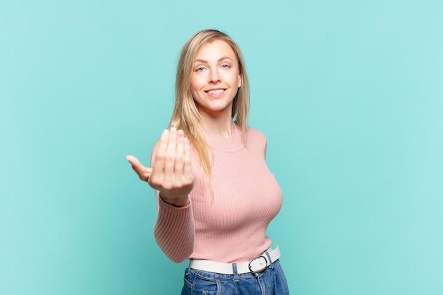 Młoda blond ładna kobieta czuje się szczęśliwa, odnosząca sukcesy i pewna siebie, mierzy się z wyzwaniem i mówi, żebyś to zrobiła! lub witam cię