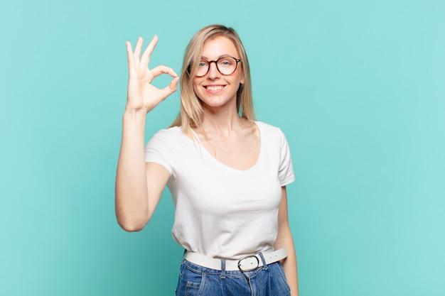 Młoda blond ładna kobieta czuje się szczęśliwa, zrelaksowana i zadowolona, okazując aprobatę dobrym gestem, uśmiechając się