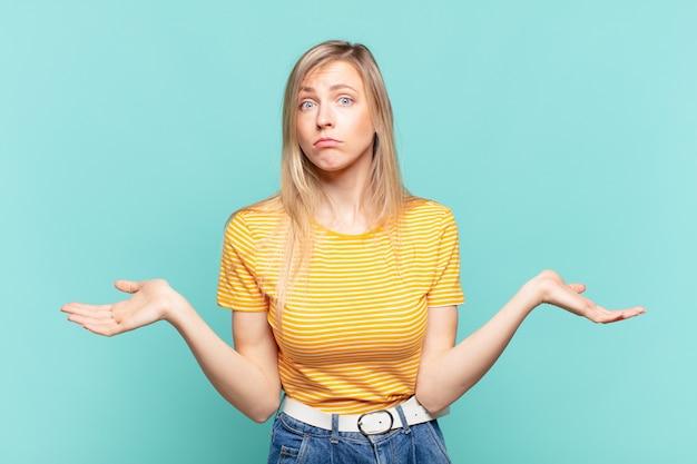 Młoda blond ładna kobieta czuje się zakłopotana i zdezorientowana, niepewna właściwej odpowiedzi lub decyzji, próbując dokonać wyboru