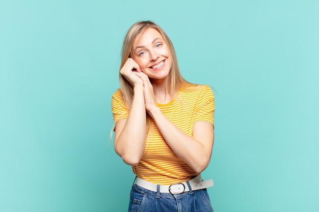 Młoda blond ładna kobieta czuje się zakochana i wygląda słodko, uroczo i szczęśliwie, uśmiechając się romantycznie z rękami przy twarzy