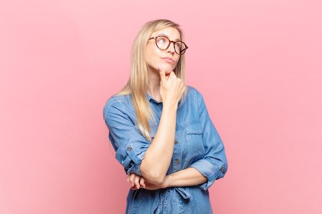 Młoda blond ładna kobieta czuje się zamyślona, zastanawia się lub wyobraża sobie pomysły, marzy i patrzy w górę, aby skopiować przestrzeń