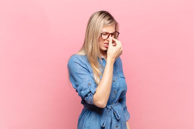 Młoda blond ładna kobieta czuje się zestresowana, nieszczęśliwa i sfrustrowana, dotyka czoła i cierpi na migrenę lub silny ból głowy