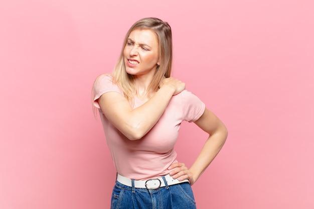 Młoda blond ładna kobieta czuje się zmęczona, zestresowana, niespokojna, sfrustrowana i przygnębiona, cierpi z powodu bólu pleców lub karku