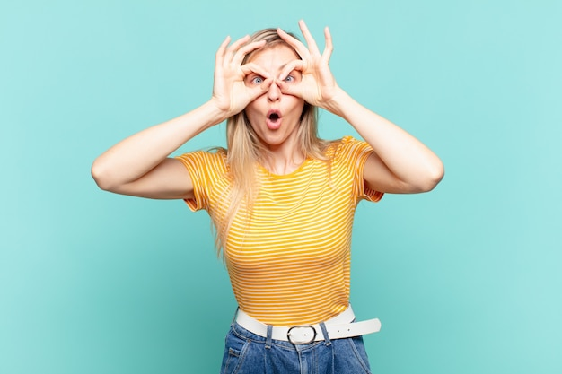 Młoda blond ładna kobieta czuje się zszokowana, zdumiona i zaskoczona, trzymając okulary ze zdumionym, niedowierzającym spojrzeniem