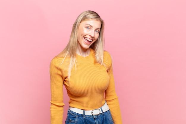 Młoda blond ładna kobieta o dużym, przyjaznym, beztroskim uśmiechu, wyglądająca pozytywnie, zrelaksowana i szczęśliwa, relaksująca