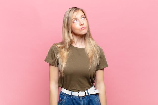 Młoda blond ładna kobieta o zmartwionej, zdezorientowanej, nieświadomej twarzy, patrząca w górę, by skopiować przestrzeń, wątpiąca