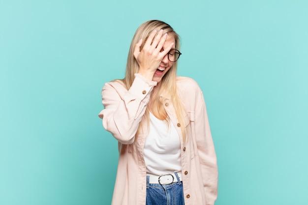 Młoda blond ładna kobieta śmieje się i klepie się w czoło, jak mówiąc dã¢â€™oh! zapomniałem lub to był głupi błąd