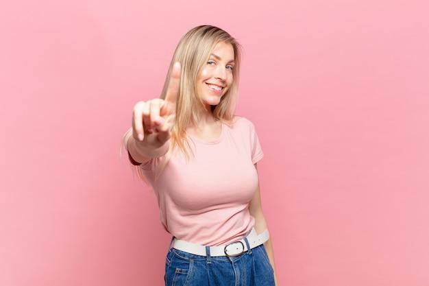 Młoda blond ładna kobieta uśmiecha się dumnie i pewnie, triumfalnie tworząc pozę numer jeden, czując się jak lider
